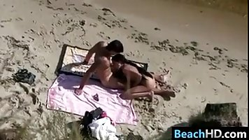 A horny man is fucking his wife, on the beach, while a voyeur is taking hot photos