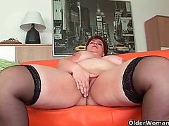 Fat, red haired granny with tattooed belly is masturbating on the couch with a blue dildo