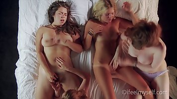Four lesbians are making love in a huge bed, instead of getting ready for work